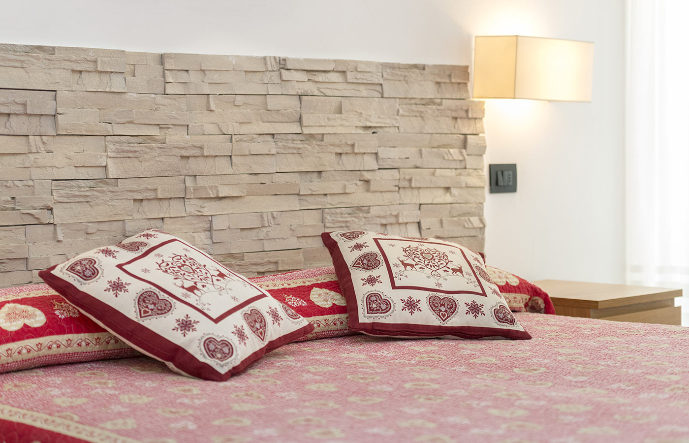 Red and white pillows on a bed of Hotel Alpino