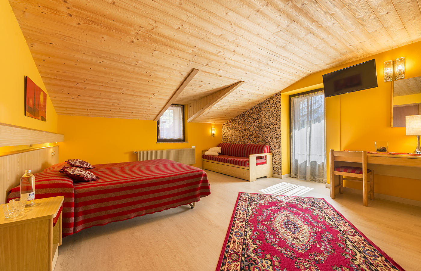 An attic room of Hotel Alpino with double bed, TV and balcony