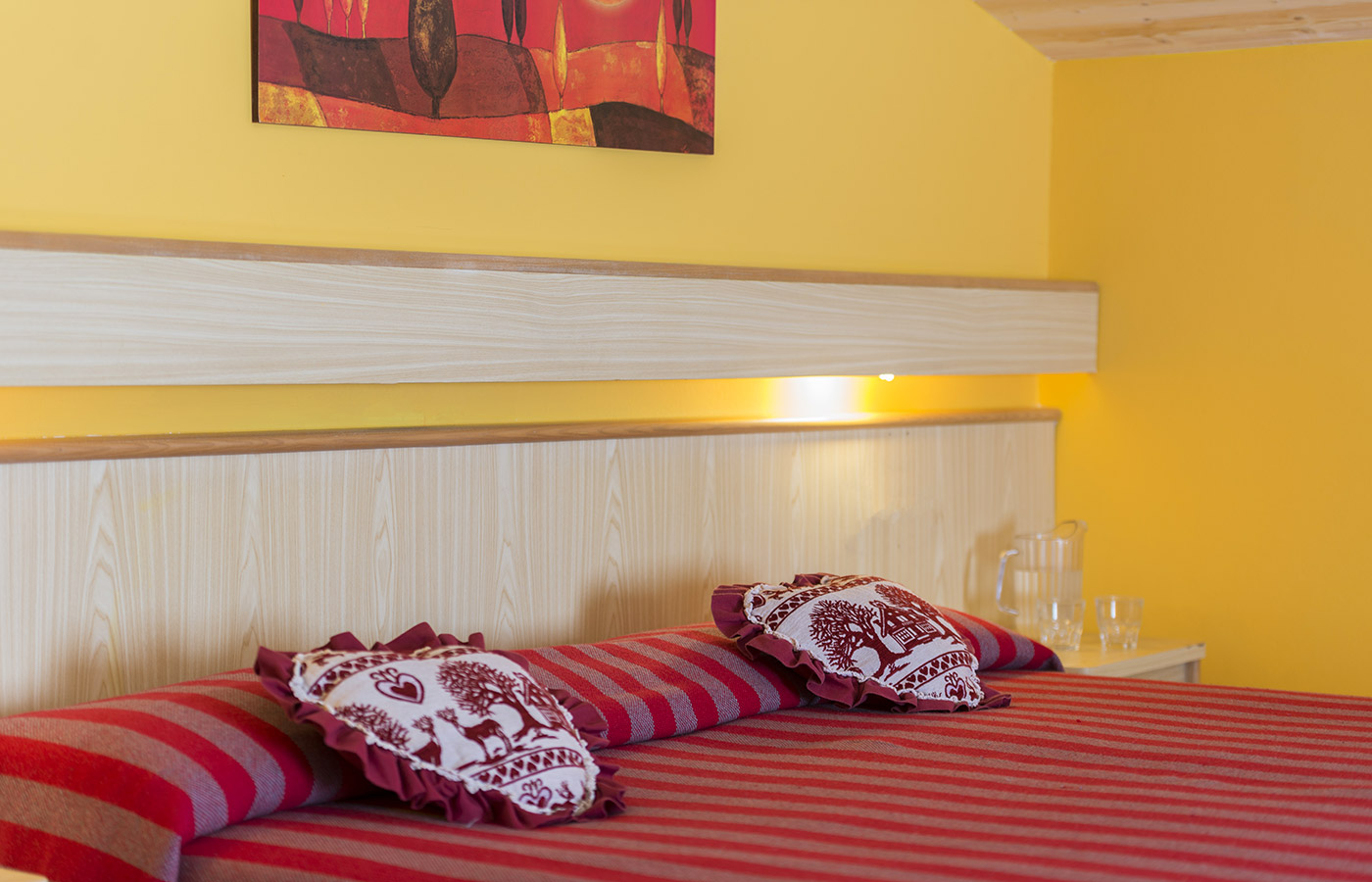 Double bed with red bedspread and cushions at Hotel Alpino