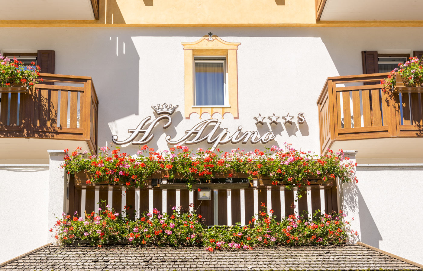 A balcony with flowers under the writing Hotel Alpino